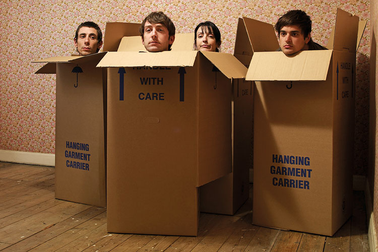 four-people-sitting-in-cardboard-boxes